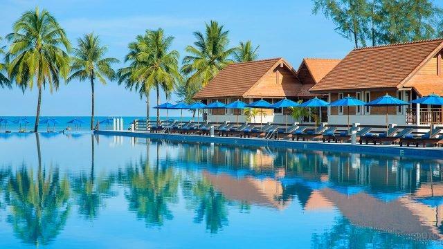 Зонтики и бунгало у бассейна пляжного отеля в заливе Пханг Нга
