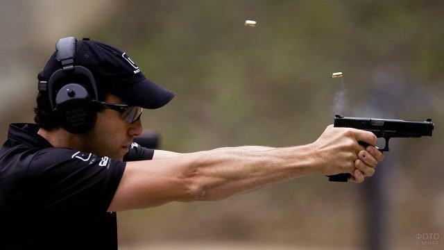 Спортсмен с пистолетом на огневом рубеже