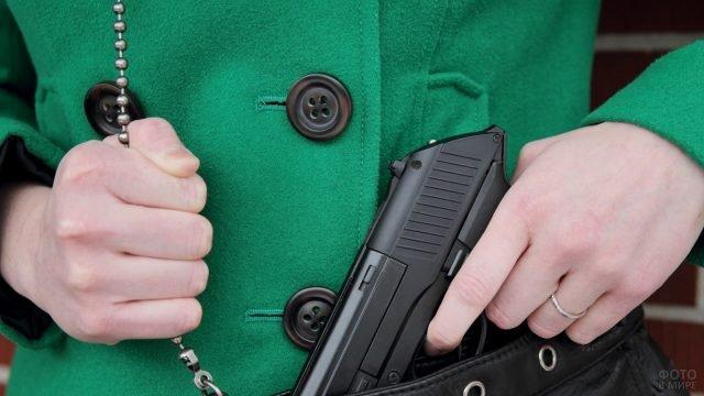 Женщина опускает пистолет в сумочку