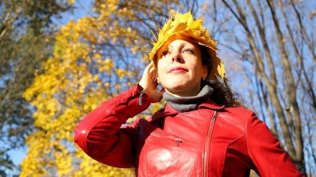 Женщина в красной куртке и жёлтом венке из кленовых листьев под кроной осеннего дерева
