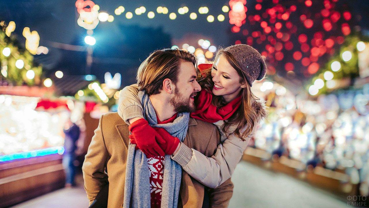 Девушка обнимает кавалера за плечи в День влюблённых на нарядной вечерней улице