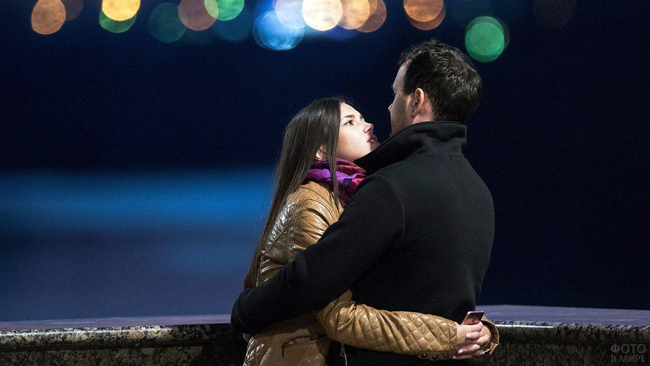 Пара обнимается на вечерней набержной в День влюблённых