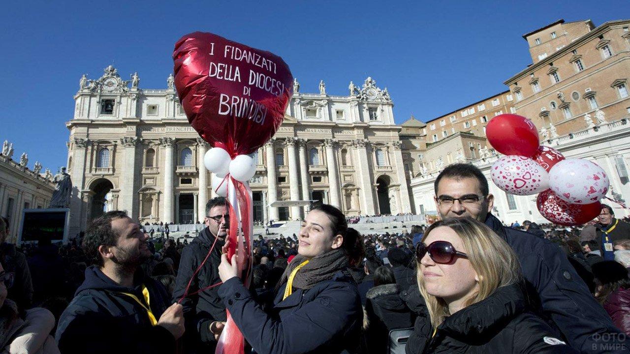 Туристы с шариками-сердечками в День влюблённых на площади в Италии