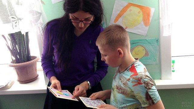 Мальчик и учительница с самодельными открытками на 8 марта