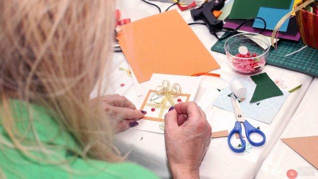 Женщина делает открытку на 8 марта в технике скрапбукинга