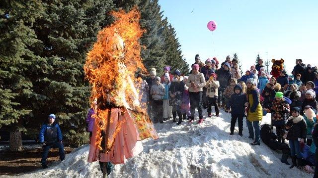 Дети на городском празднике Масленицы смотрят на сжигание чучела Зимы