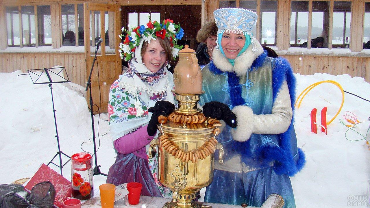 Две красивых женщины в народных костюмах у самовара на Широкой Масленице