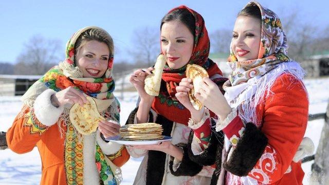 Красивые девушки в национальных костюмах едят масленичные блины на народном гулянье