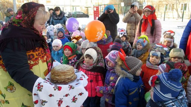 Воспитанники детского сада угощаются блинами на утреннике в честь Масленицы