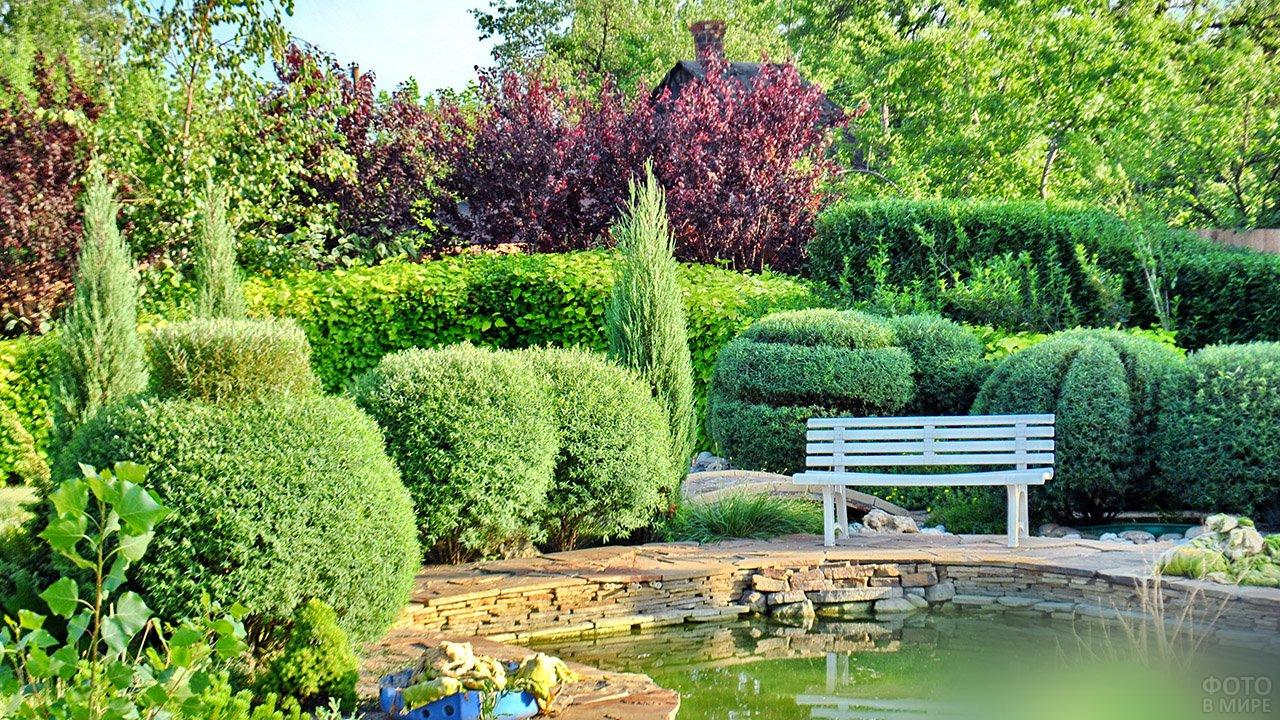 Белая скамейка у пруда в оформлении регулярного сада