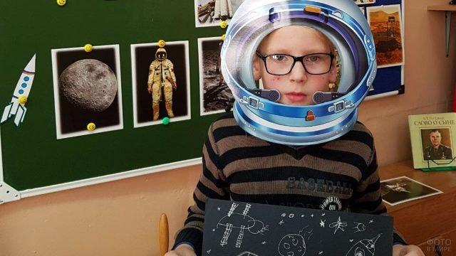 Первоклассник с самодельной открыткой к 12 апреля на фоне стенда к Дню космонавтики