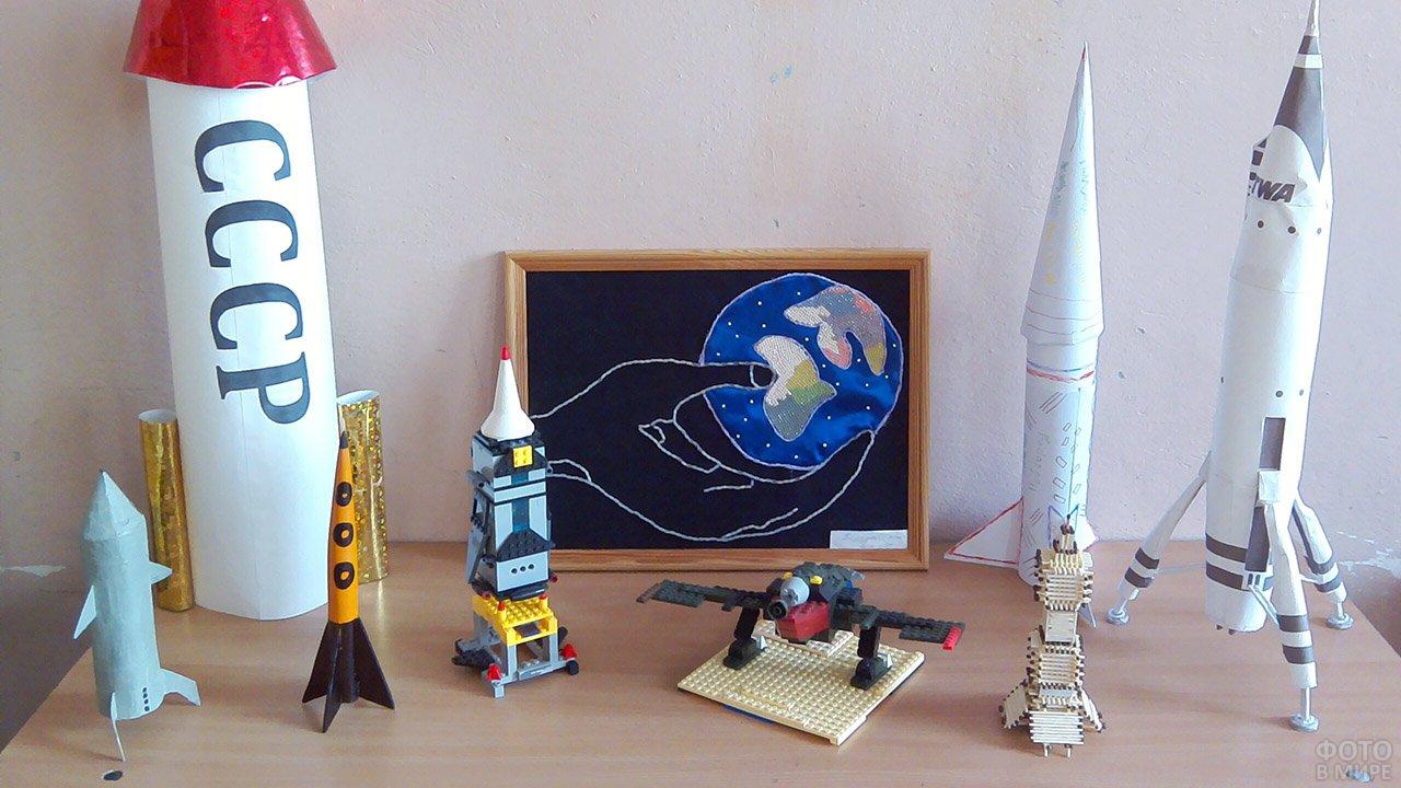 Поделки-ракеты на фоне самодельной открытки на выставке к 12 апреля