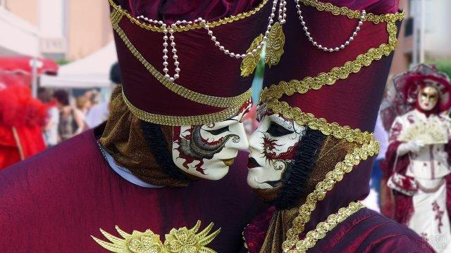 Целующаяся пара в венецианских масках на праздничном карнавале 14 февраля