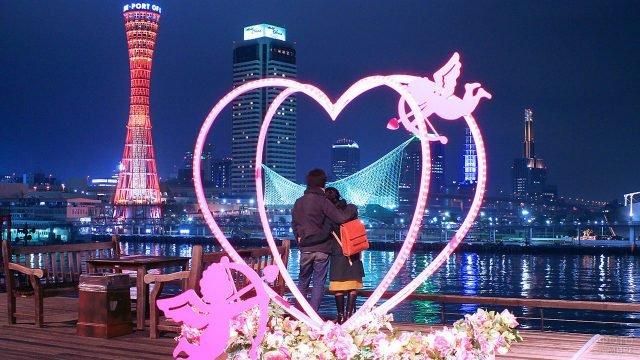 Пара на набережной в Токио в День влюблённых среди огней