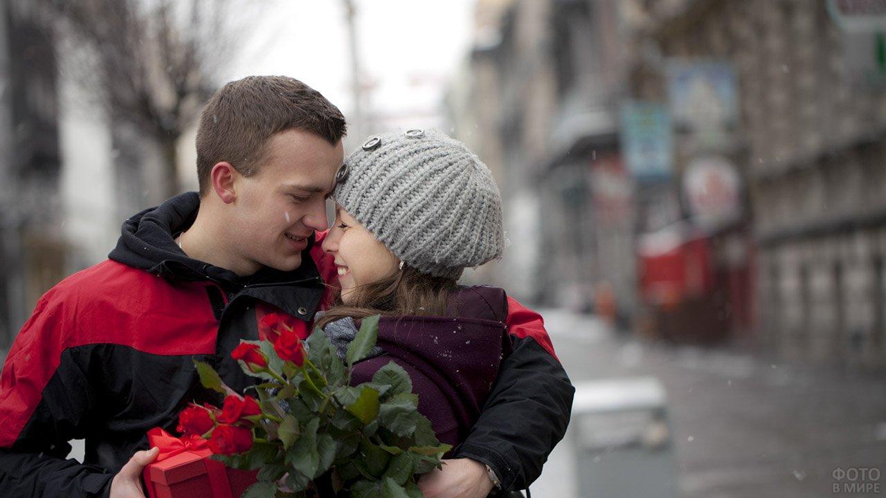 Пара с продарками под лёгким снегопадом в День влюблённых