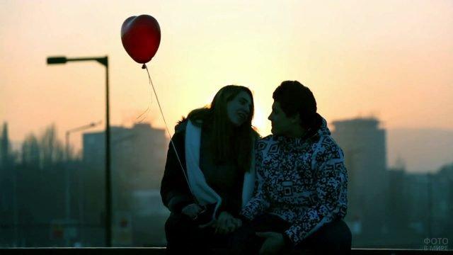 Парочка с шариком в форме сердечка на фоне заката в День влюблённых