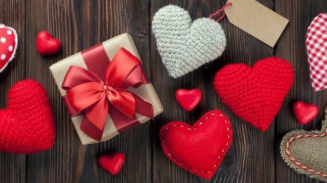 Сувениры и валентинки к 14 февраля на деревянном фоне