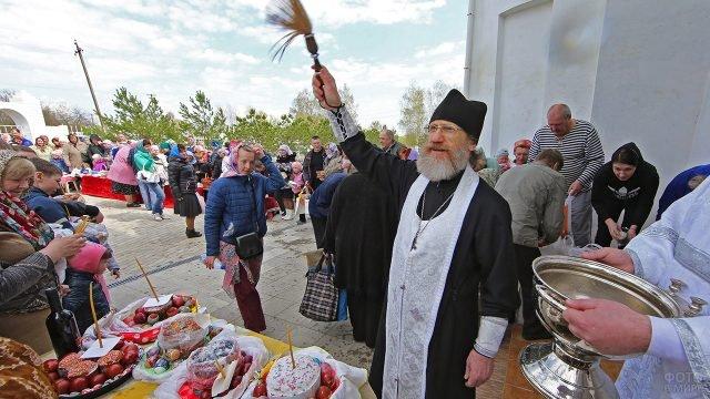 Прихожане с пасхальными угощениями и освящающий их батюшка у порога церкви