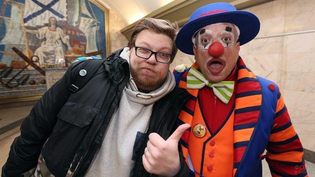 Аниматор в костюме клоуна с пассажиром метро в День смеха