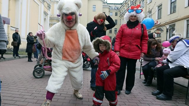Аниматоры в маскарадных костюмах развлекают семьи с детьми в День смеха на улице Питера