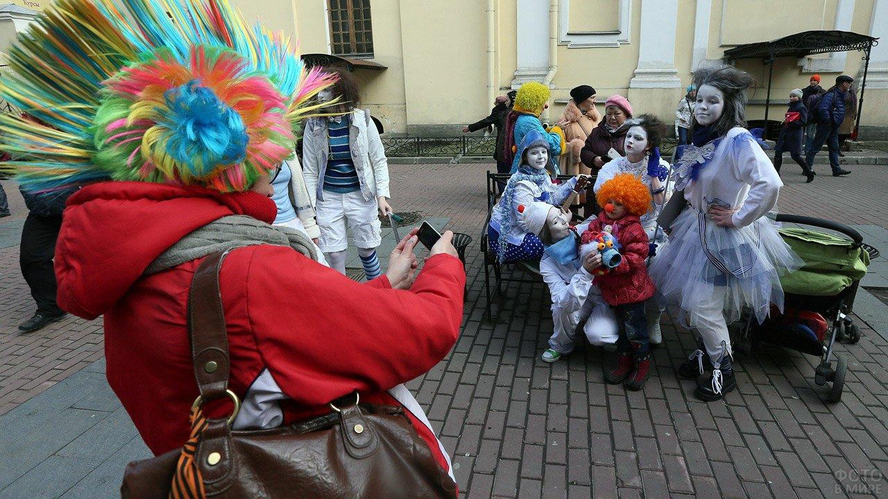 Группа мимов с малышом в клоунском костюме на уличном параде в честь 1 апреля