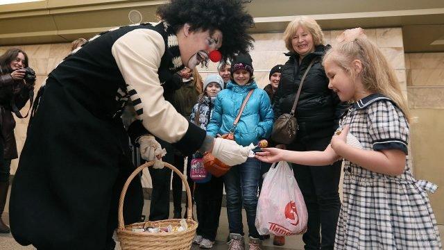 Клоун раздаёт детям конфеты в День смеха в Петербургском метро