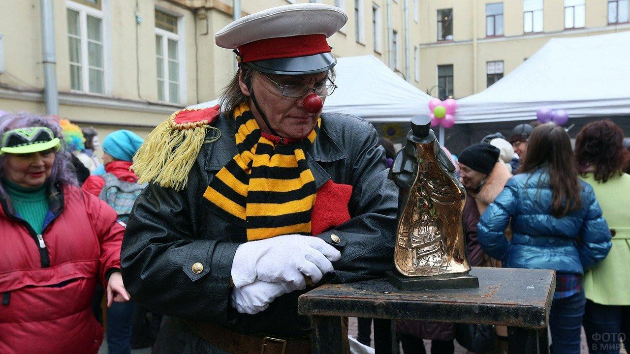 Клоун в фуражке на улице Питера в День смеха