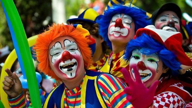 Участники парада на 1 апреля в Париже в костюме клоунов