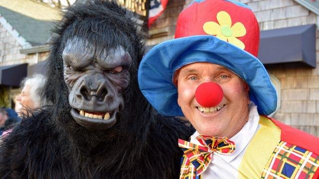 Участники уличного парада в День смеха в костюмах клоуна и гориллы