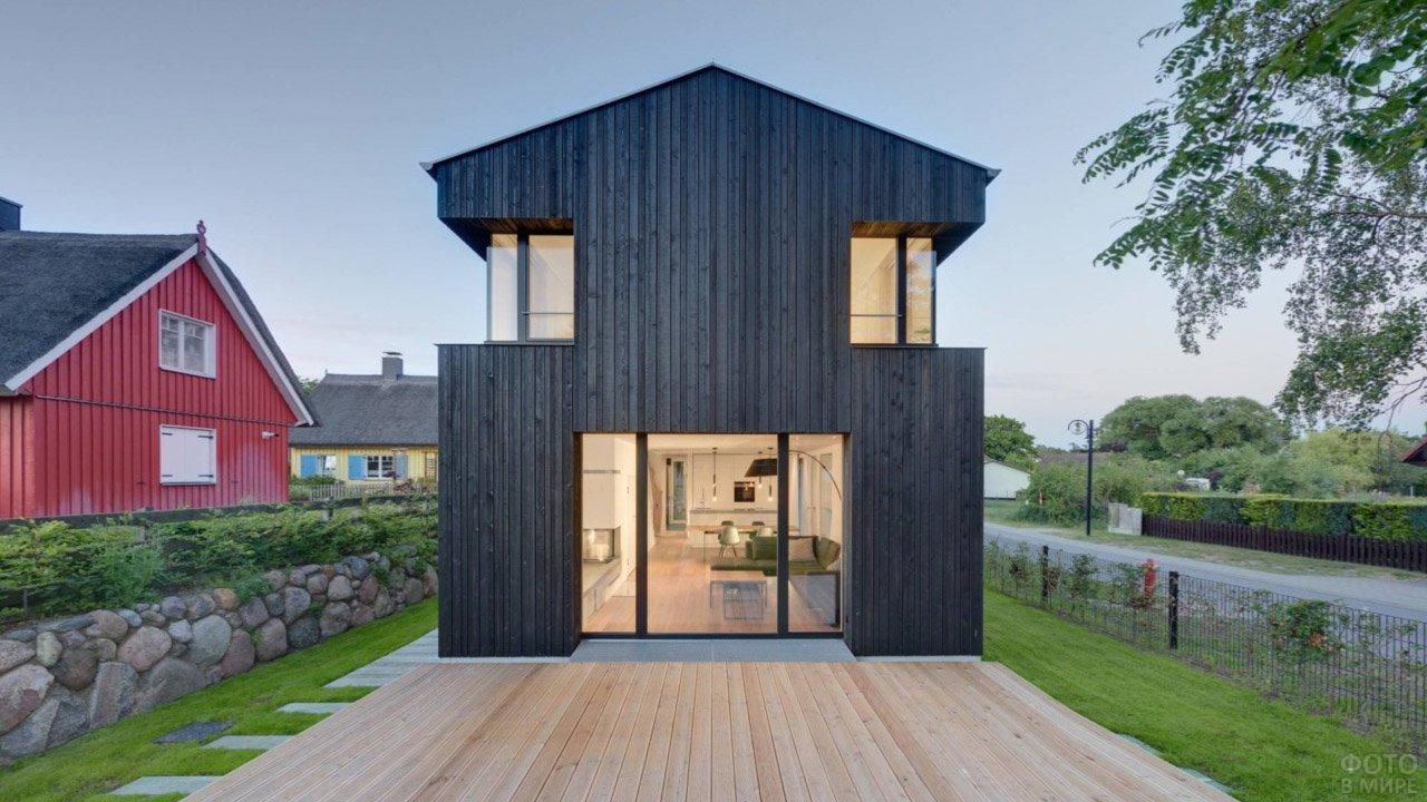 Чёрный фасад деревянного двухэтажного дома в скандинавском стиле