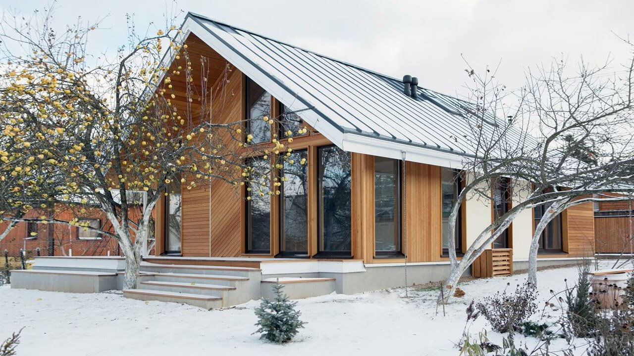 Каркасный дом в скандинавском стиле на участке с яблонями поздней осенью
