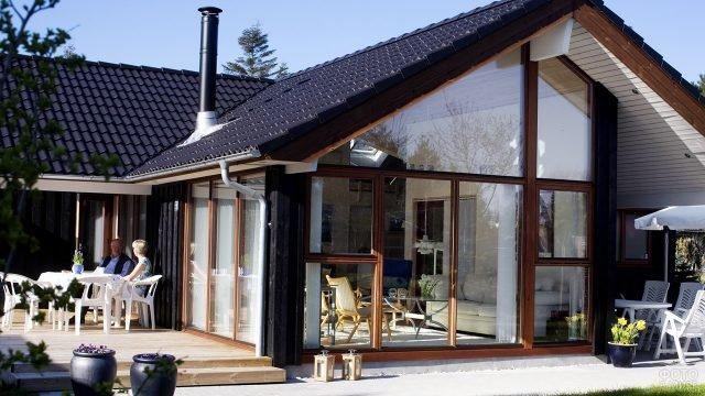 Пожилая пара на веранде скандинавского дома с французским остеклением фасада