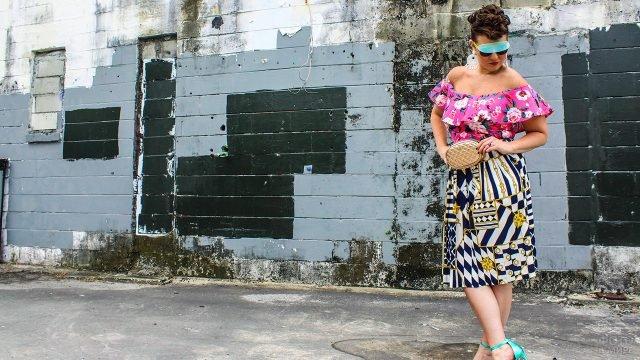 Модель размера плюс-сайз в блузке с воланом и пёстрой юбке по моде 80-х