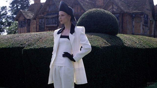 Модель в белом костюме с чёрными аксессуарами коллекции 1986 года