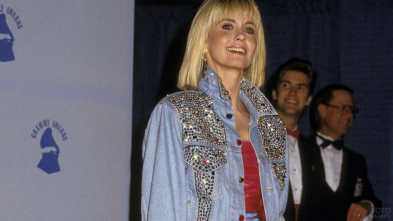 Модная в 80-х джинсовая куртка с клёпками и стразами на современной блондинке