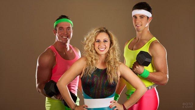 Женщина и два атлета демонстрируют костюмы для аэробики из 80-х
