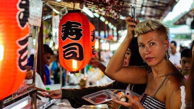 Туристка пробует блюда местной кухни на Золотом базаре