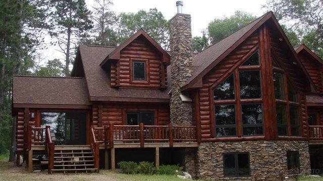 Бревенчатый дом-шале с каменной отделкой каминной трубы и цоколя