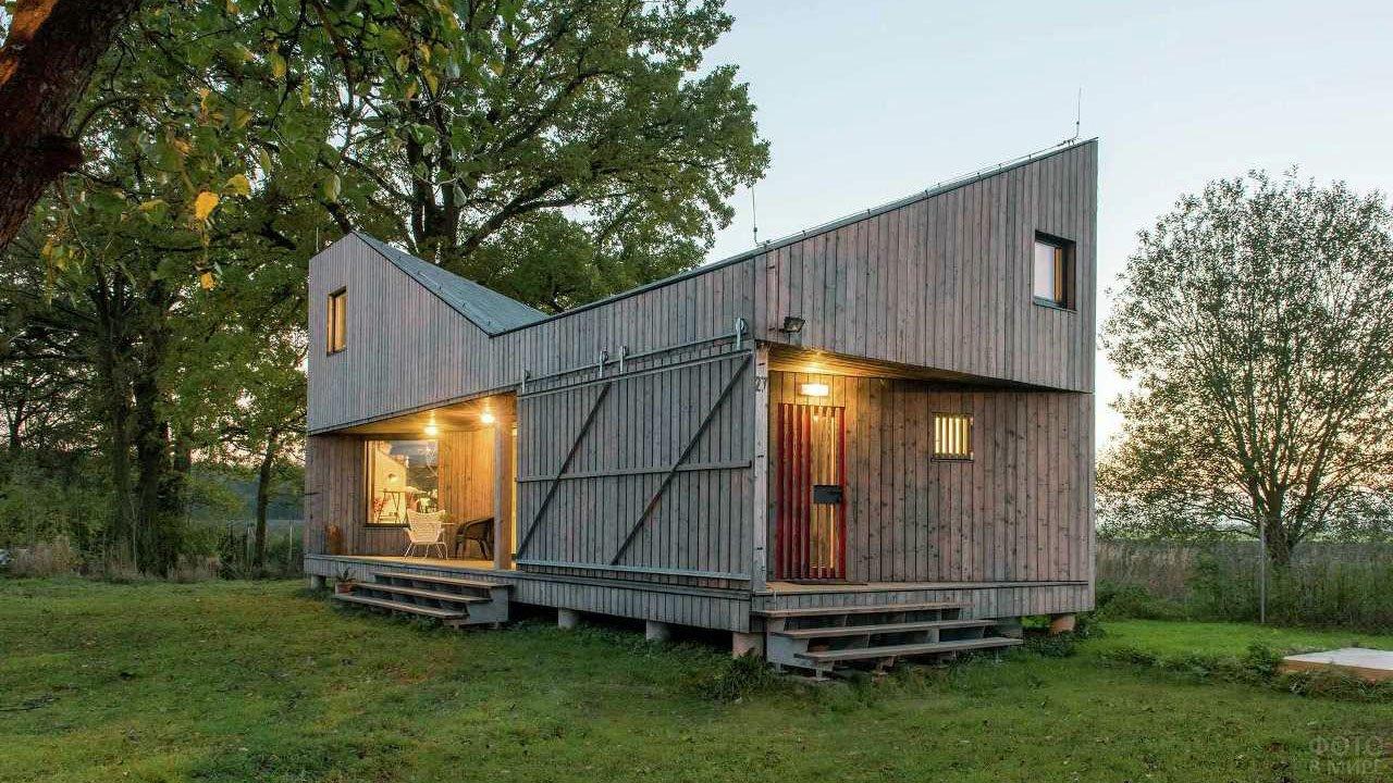 Дачный домик в современном стиле Барнхаус на лужайке под деревьями