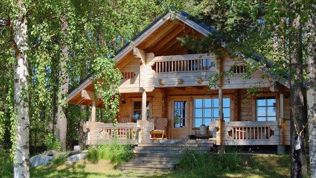 Деревянный дом-шале с широким крыльцом среди берёз