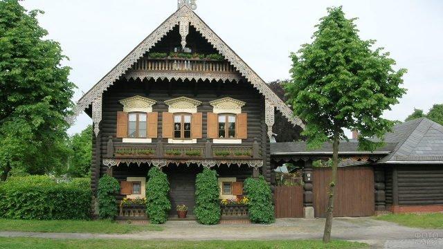 Деревянный дом современной постройки с резными наличниками и карнизами в русском стиле