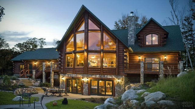 Просторный многоуровневый деревянный дом в стиле шале на каменных сваях