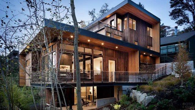 Современный минималистичный деревянный дом на склоне холма