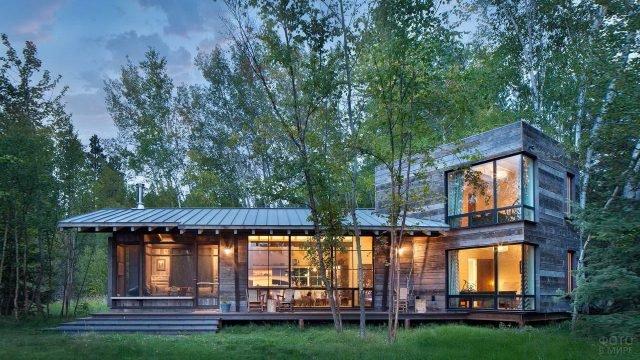 Современный модульный дом из дерева посреди зелёного леса