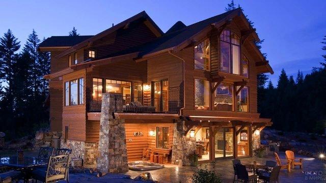 Трёхэтажный деревянный дом с частичной отделкой декоративным камнем