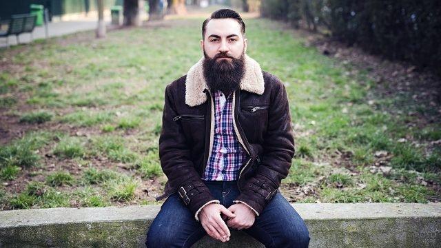 Аккуратно постриженный молодой мужчина с окладистой бородой