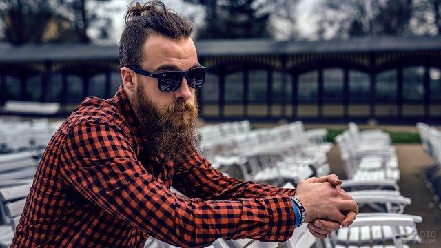 Бородатый мужчина в клетчатой рубашке и солнечных очках