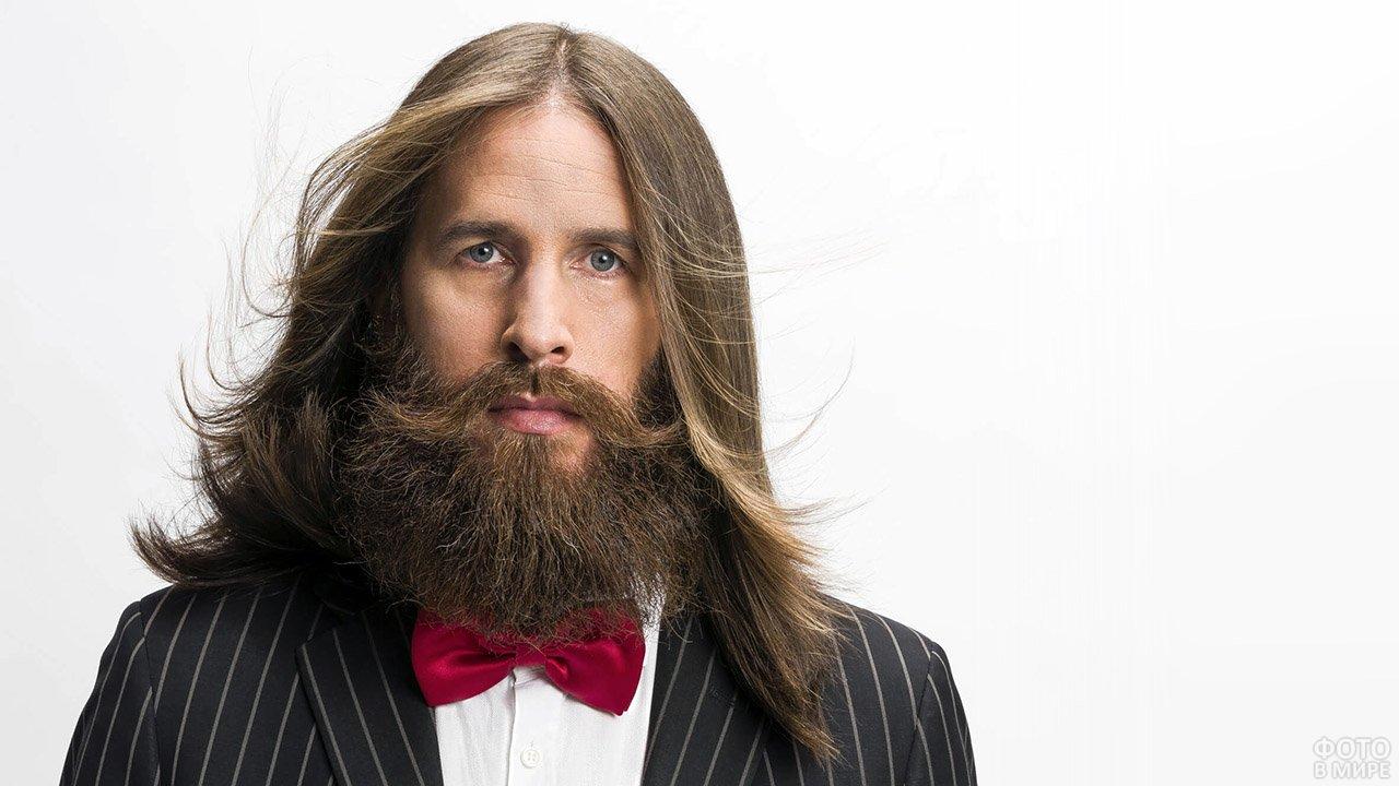Длинноволосый мужчина с густой бородой в костюме с бабочкой
