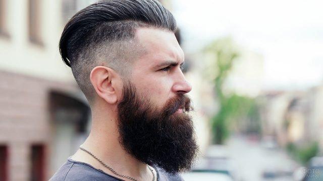 Хипстер с модной стрижкой и окладистой бородой