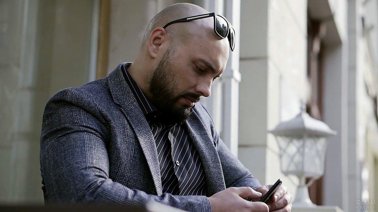 Лысый мужчина с бородой смотрит в смартфон
